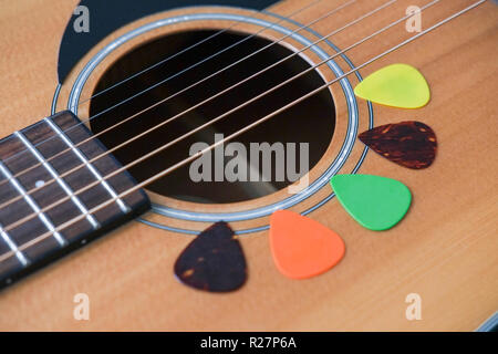 Acoustic guitar with a variation of guitar plectrums - Stock Image