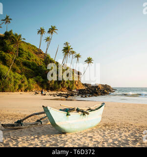 Traditional wooden boat on Talalla Beach at dusk, South Coast, Sri Lanka, Asia - Stock Image