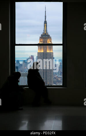 People observing The Empire State Building through a window of the  Rockefeller Centre during the evening, New York, America, USA. - Stock Image