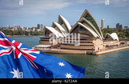 Australian flag flying in front of Sydney Opera House. Composite image. - Stock Image