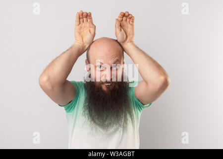 Portrait of funny crazy middle aged bald man with long beard in light green t-shirt standing with bunny ears gesture and looking at camera. indoor stu - Stock Image