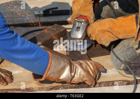 Worker cuts a metal structure with an electric flex - Stock Image