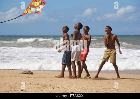Boys kite-flying at Easter on the beach at Blanchisseuse - Stock Image