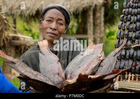 Woman Selling Fish, Smoked Tilapia (Ngege), Roadside Fish seller, Street Vendor, Vendors Uganda - Stock Image