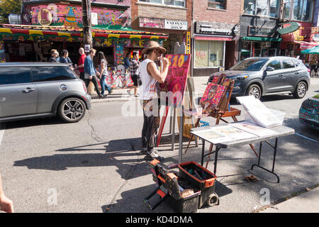 Street artist paints on his easel on Augusta St in Kensington Market in downtown Toronto Ontario Canada - Stock Image