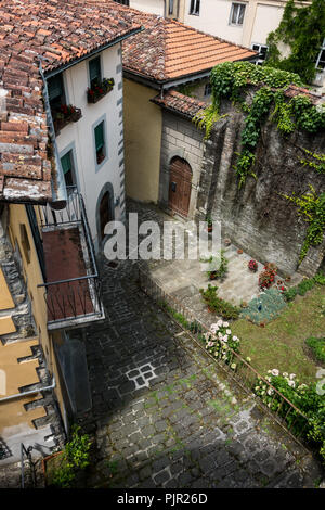 Old Carved Stone Face set into a wall in Barga, Tuscany, Italy - Stock Image