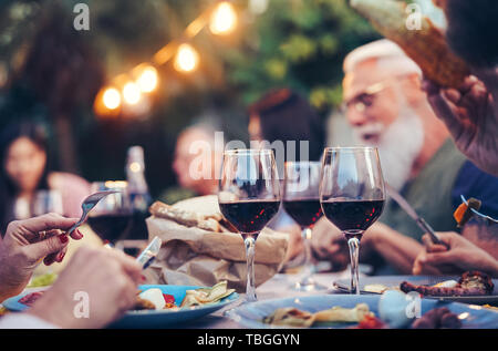 Happy family eating and drinking red wine at dinner barbecue party outdoor - Mature and young people dining together on rooftop - Stock Image
