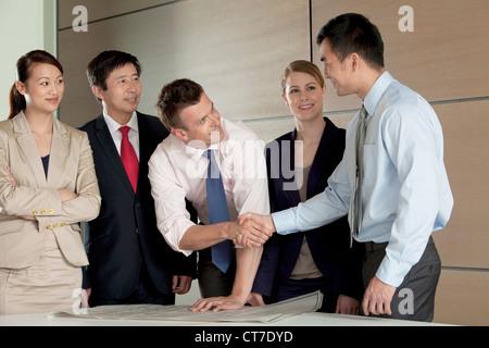 Multi racial businesspeople shaking hands over blueprint - Stock Image