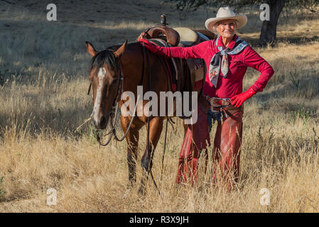 USA, California, Parkfield, V6 Ranch cowgirl dressed in a red shirt, chaps, and a hat standing by her brown horse (MR) - Stock Image