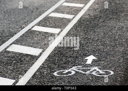 Separate bicycle lane for riding bicycles. White painted bike on asphalt. Ride ecological green urban transport - Stock Image