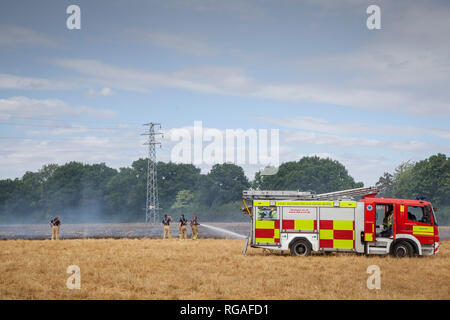 Firemen and appliances from Royal Berkshire Fire and Rescue Service attend a stubble fire near Kidmore End, Oxfordshire - Stock Image