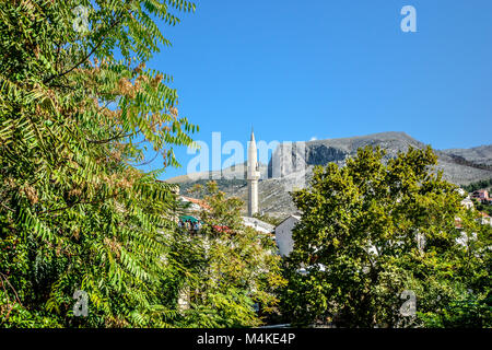 A white minaret towers over old town Mostar Bosnia and Herzegovina near the old bridge on a sunny summer day. - Stock Image