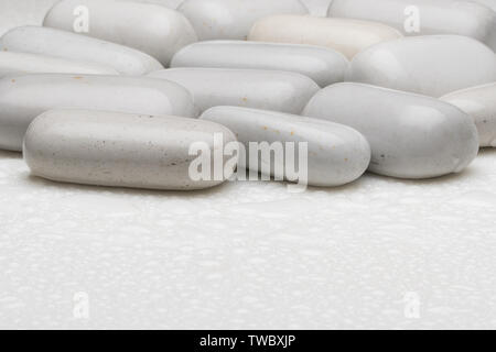white smooth stones with water drops on light background - Stock Image