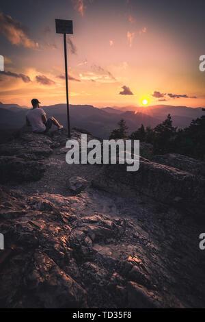 Man on top of mountain. Conceptual scene. - Stock Image