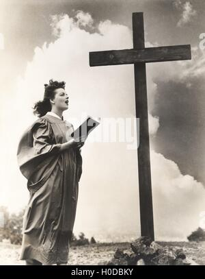Woman singing hymns by a large wooden cross on a hill - Stock Image