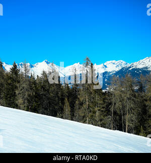Squared image of empty ski mountain snow slope landscape with beautiful conferous forest and blue sky. Kronplatz, Dolomites, South Tyrol, Italy. - Stock Image