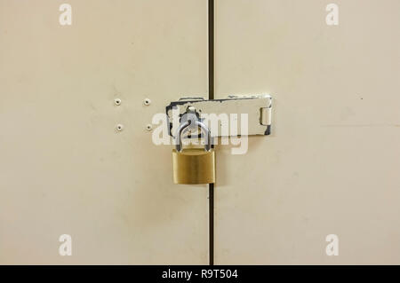 Padlock on closed metal door. - Stock Image