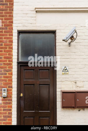 CCTV surveillance camera mounted on a wall outside an entrance door to residential flats in Southampton, England, UK - Stock Image