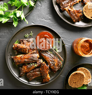 Tasty grilled spare ribs on plate over black stone background. Top view, flat lay - Stock Image