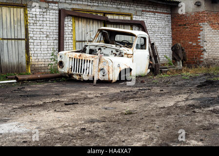 Broken and scrapped white lorry truck cabin used for salvaging parts rests outside a brick garage. - Stock Image