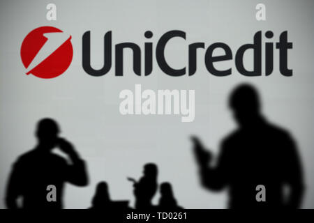 The UniCredit logo is seen on an LED screen in the background while a silhouetted person uses a smartphone in the foreground (Editorial use only) - Stock Image