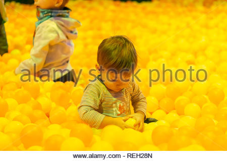 Kownaty, Poland - January 6, 2019: Young toddler boy sitting between many yellow plastic balls in a playground in the indoor Majaland attraction park. - Stock Image