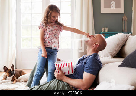 Girl stands feeding dad popcorn, watched by pet dog at home - Stock Image