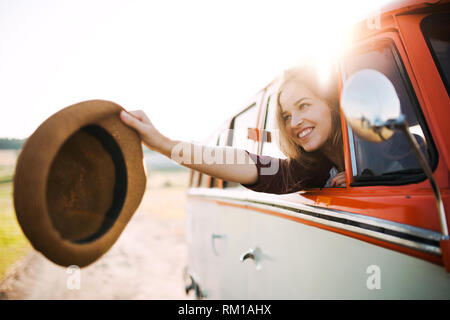 A young girl looking out of a car on a roadtrip through countryside. - Stock Image