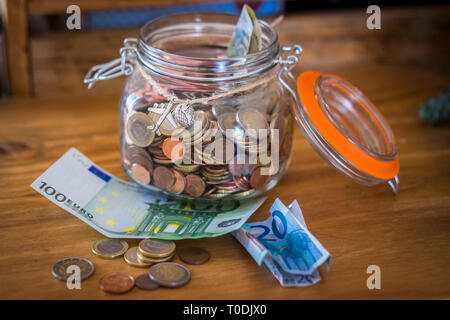 glass vase full of money cash and coins ready to be used to travel or realize dreams for people - modern society business concept - Stock Image