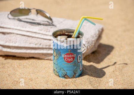 Bournemouth, UK. 26th June 2018. UK Weather, a heatwave in June. Sandy beach in Bournemouth with towel, shades and a rum and coke drink. Credit: Thomas Faull / Alamy Live News - Stock Image