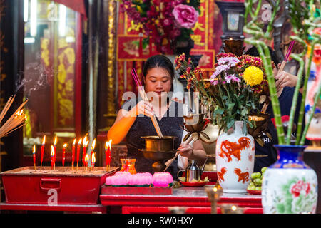 Sin Sze Si Ya Taoist Temple, Chinatown, Kuala Lumpur, Malaysia.  Woman Lighting Joss Sticks. Oldest Taoist temple in Kuala Lumpur (1864). - Stock Image