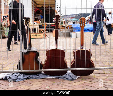 Three guitars for sale in the market on NDSM in Amsterdam - Stock Image