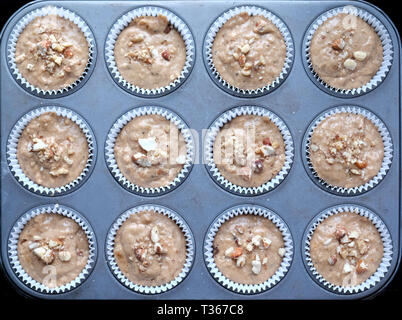 overhead view of 12 baking mix cup cakes in white paper cases on a metal baking tray about to go into the oven, the cakes and baking tray are very sym - Stock Image