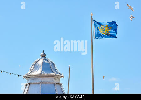 The flag of Brighton and Hove region on a sunny day at the seaside promenade in Brighton. - Stock Image