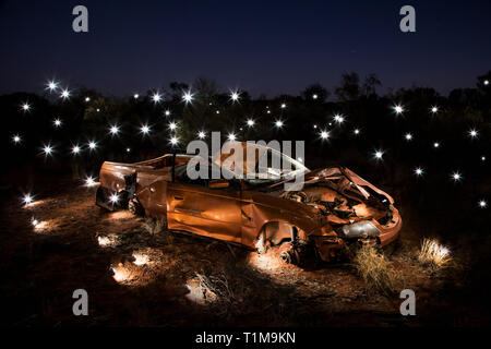 Lights illuminating art installation of crushed car - Stock Image