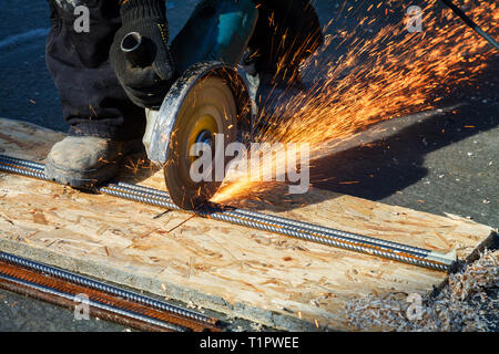 An employee in white overalls and a protective mask processes with electric flexion a metal structure - Stock Image