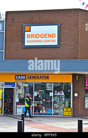 Welcome Sign outside the modern Bridgend Shopping Centre, above the Cash Generator shop. Man in high vis jacket walking past. - Stock Image