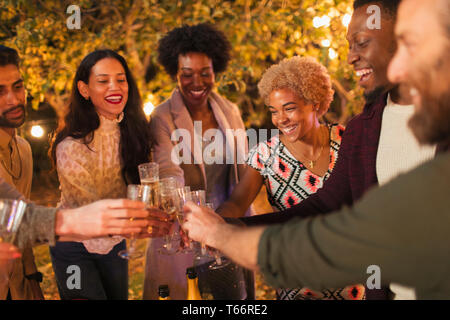 Happy friends celebrating, toasting champagne at dinner garden party - Stock Image
