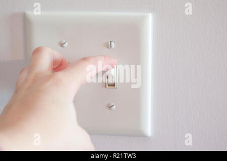 Hand about to turn a light switch from the on position to off - Stock Image