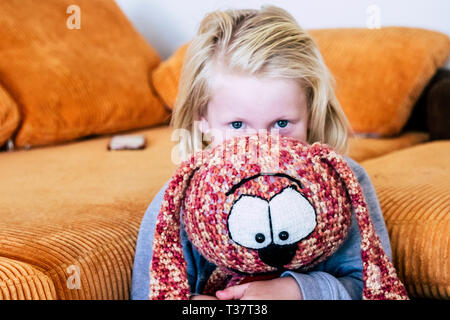 Young playful blonde caucasian children play with puppy at home - childhood lifestyle and colors in background - Stock Image