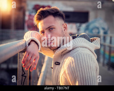 Handsome trendy young man, standing on a sidewalk in city - Stock Image
