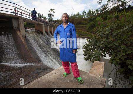 Technicians inspect dam upstream of hydro electric powerplant, Rwanda - Stock Image