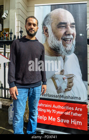 London, UK. 10th August 2018. Ali Mushaima who has been on hunger strike at the Bahrain embassy since the start of August to save his fathers life stands in front of a banner with a photograph of his father at the vigil by Inminds Islamic human rights organisation vigil calling for the immediate release of Hassan Mushaima and all the other 5000 Bahraini prisoners of conscience languishing in the Al-Khalifa regimes jails. They also demanded the British government end its complicity in the Al Khalifa dictatorship's crimes against the Bahraini people. Credit: Peter Marshall/Alamy Live News - Stock Image
