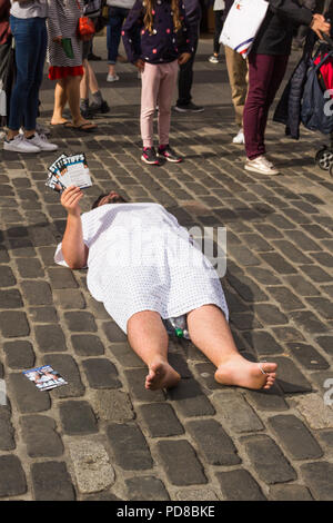 Edinburgh, Scotland, UK. 7th August 2018. Street acts and artists, alongside promoters of Fringe Festival events, ply the streets of Edinburgh Festival, providing entertainment and amusement to the many visitors to the Fringe. Lying prone in the street proves and effective way of promoting the new comedy 'Stiffs'. Credit Joseph Clemson, JY News Images/Alamy. - Stock Image
