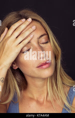 Young woman touching her forehead with eyes closed - Stock Image