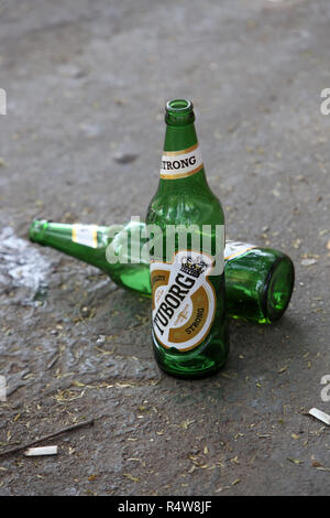 Empty beer bottles and used cigarettes left by irresponsible tourists at a tourist place. - Stock Image