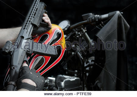 Modern Weapon Held Over a Custom Flame Painted Bikie Style Motorcycle - Leather Vest - i - Stock Image