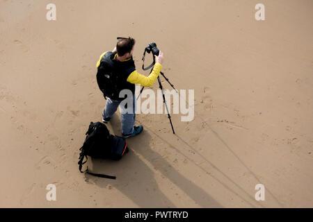 Landscape photographer on Saltburn Beach setting up his camera on a tripod on Saltburn Beach - Stock Image