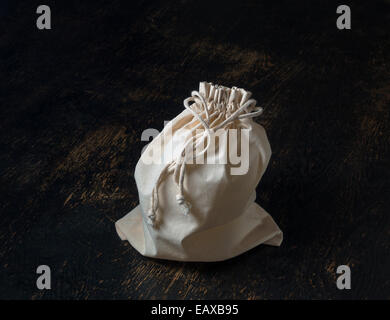 tied closed drawstring bag on wood table - Stock Image