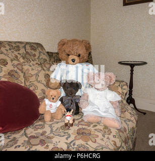 Group of bears and donkey on settee - Stock Image